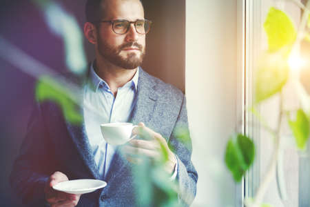 handsome businessman drinking morning coffee at office Stock Photo