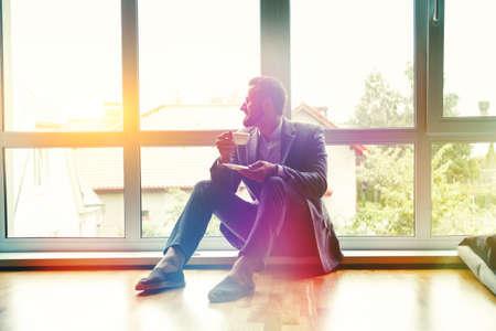 handsome businessman drinking morning coffee near window in sunlight Stock Photo