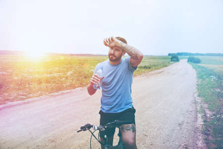 handsome man riding bike and drinking water resting Reklamní fotografie