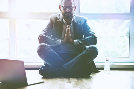 businessman doing yoga in lotus pose at office workplace with laptop