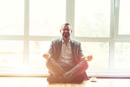 businessman doing yoga in lotus pose