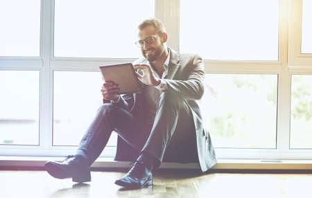 cheerful businessman with digital tablet sitting near window