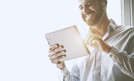 smiling businessman with digital tablet and earphones Stock Photo