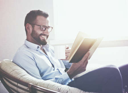 smiling handsome man reading book drinking coffee or tea Stock Photo