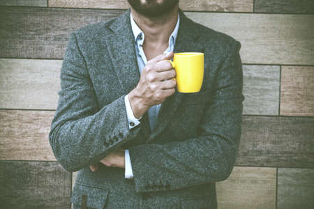 businessman hand holding morning coffee at wall background