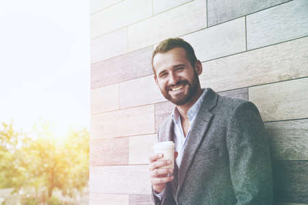 portrait of handsome businessman having break holding morning paper cup of coffee