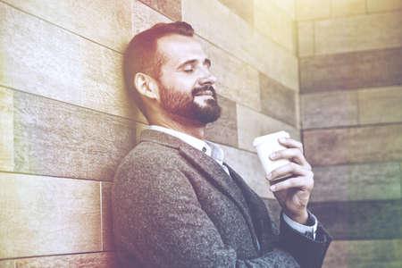 コーヒーの朝紙コップを持って休憩を持つハンサムな実業家