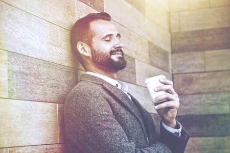 handsome businessman having break holding morning paper cup of coffee Stock Photo