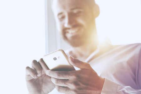Handsome businessman using smart phone in sunlight Stock Photo