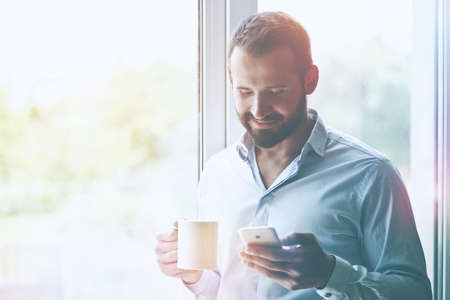 businessman holding morning coffee and reading phone Stock Photo