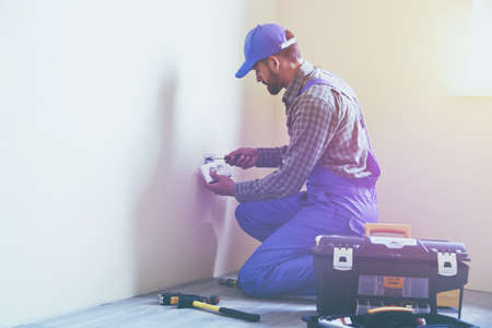 Service man installing power socket in wall with screwdriver. Copy space for text