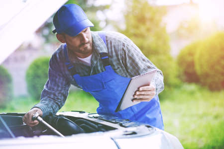 Auto mechanic working with digital tablet and wrench in engine. Car repair service with digital inspection