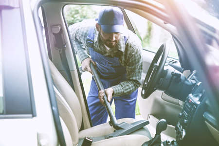 service man with vacuum cleaner cleaning car sea Stock Photo