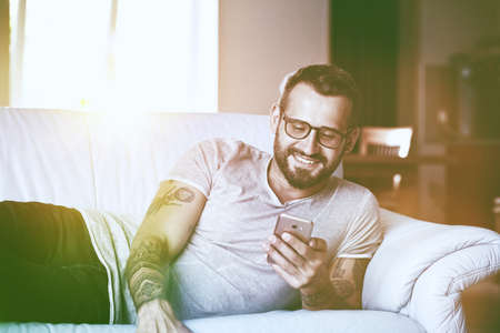 smiling man with smart phone lying on couch