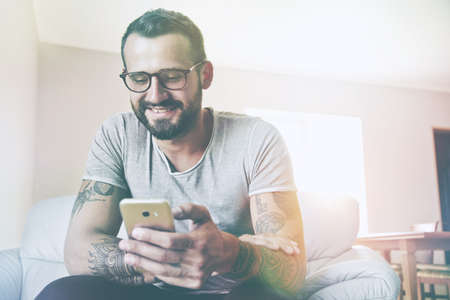 smiling man with smart phone sitting on couch