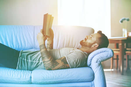 man reading book lying on sofa at home in morning sunlight