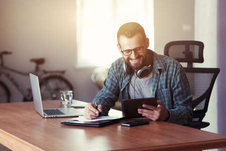 smiling man with digital tablet, headphones and pen at table Stock Photo