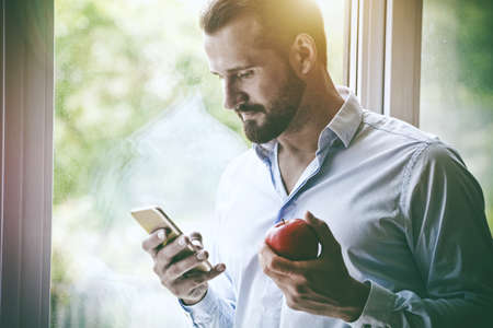 handsome businessman using smart phone and eating apple Stock Photo