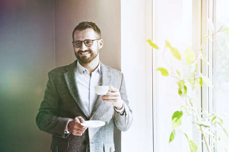 handsome businessman holding morning cup of coffee