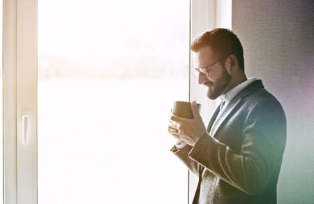 handsome businessman holding morning cup of tea or coffee, copyspace Stock Photo