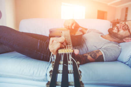 handsome man playing acoustic guitar lying on sofa