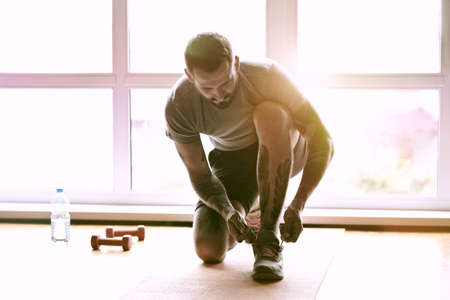 handsome sporty man getting ready for training tying shoes laces Stock Photo