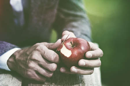 male hands peeling red apple with knife