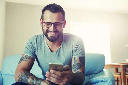smiling man with smart phone sitting on sofa Stock Photo