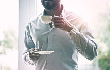 businessman hand holding cup of coffee