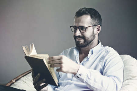 Handsome man reading interesting book Stock Photo