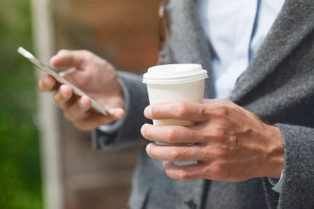 businessman hand holding morning coffee and reading phone