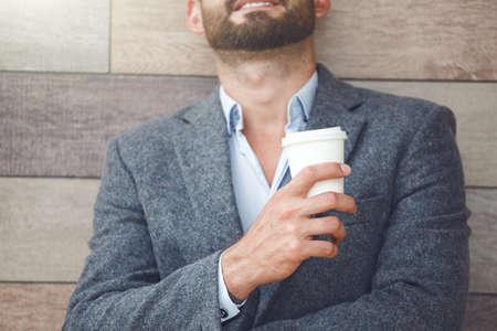 コーヒーの朝紙コップを持って休憩を持つハンサムな実業家。