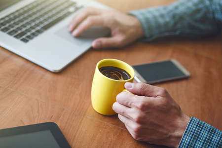 man drinking cup of morning coffee at table with laptop Stock Photo