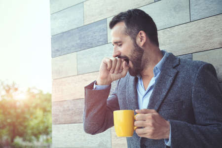 businessman yawning and holding morning coffee at wall background