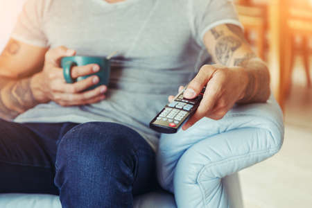 man drinking tea and  watching tv with remote control