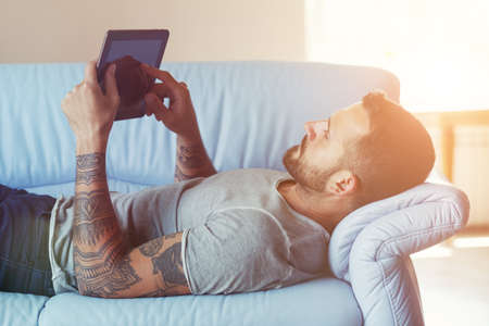 man lying on sofa with digital tablet pc at home