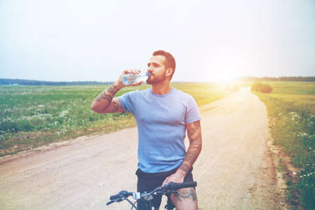 handsome man riding bike and drinking water resting Stock Photo