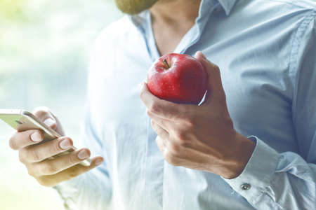 businessman hands using smart phone and eating apple