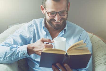 smiling man reading interesting book