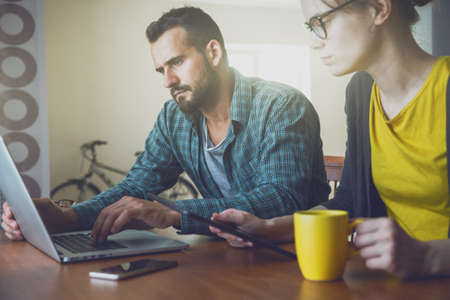 smiling man and woman working together with laptop