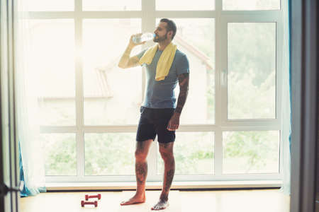 Handsome sporty man resting, having break drinking water after doing exercise