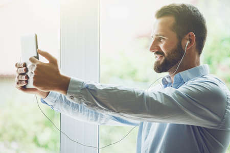 smiling businessman with digital tablet and earphones calling with video conference