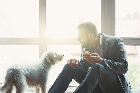 Handsome businessman with smart phone and cute dog
