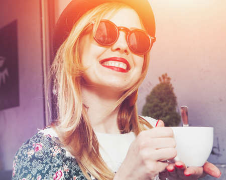 cheerful girl drinking coffee in morning sunlight