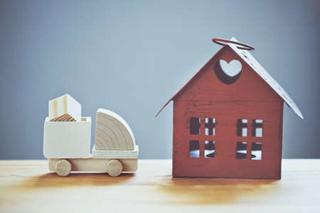 Wooden model of caargo truck delivering box to house. Shipping and transportation concept
