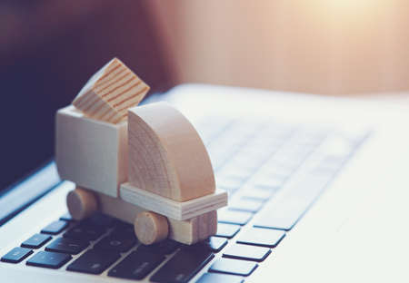 Wooden toy truck on laptop keyboard. Internet shopping, on-line purchase, e-commerce and packages delivery concept. Stock Photo