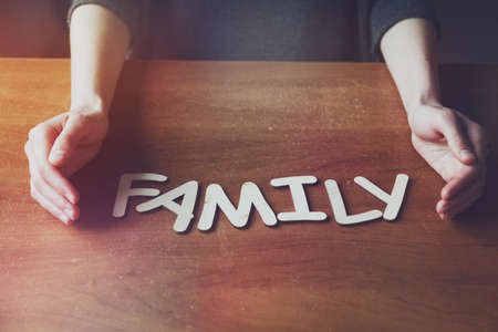 womans hands protecting Family word