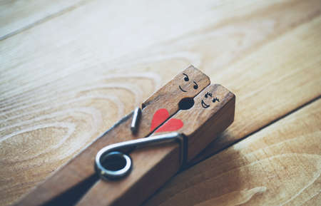 Happy couple in love. Wooden pin with painted funny faces of lovers.