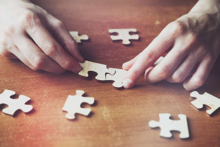 hands solving jigsaw puzzle with wooden pieces Stock Photo