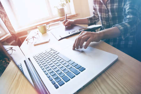 designers hands with tablet and laptop at table Stock Photo